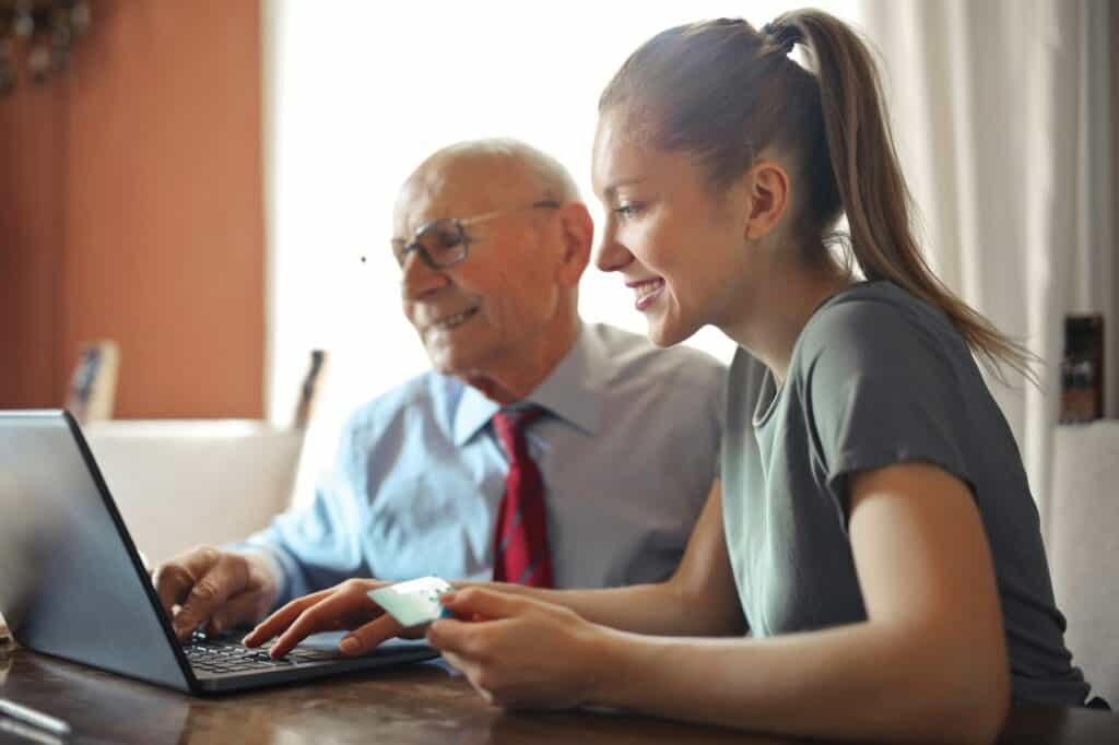Woman with elderly man looking at a computer.